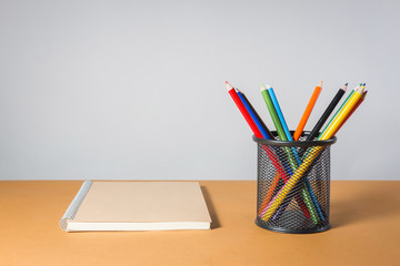 A stack of color pencils and notebook