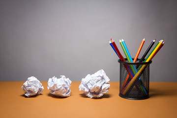 A stack of color pencils and crumpled paper. Business frustrations, Job stress and Failed exam concept.