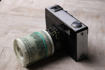 Conceptual photo for microstock photography, making money by camera shooting. Camera and Money