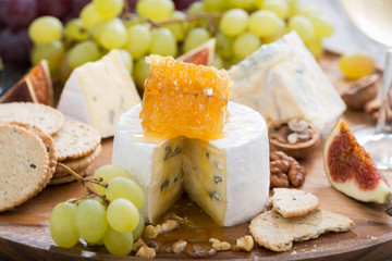 camembert with honey and fruit, snacks on a wooden tray
