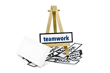 concept teamwork word on wooden stand.random cutted print paper and empty canvas frame isolated white background