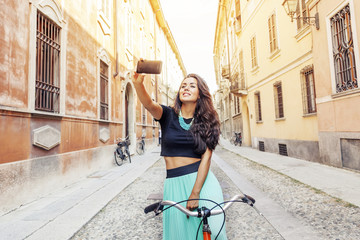 pretty young girl with a bike takes a selfie around town