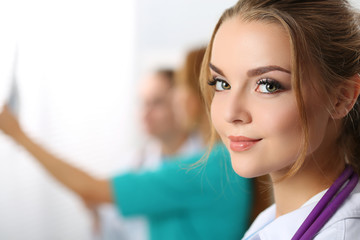 Beautiful smiling female medicine doctor looking in camera