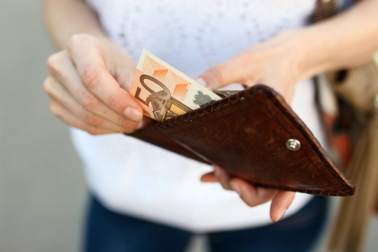 Girl is taking out fifty-euro banknote from her leather wallet