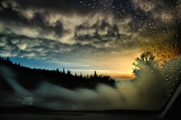 A sunset in a mountain area, seen trough the windscreen of a car, on which raindrops and steaming are visible.