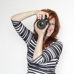 Woman taking a photograph with a reflex camera