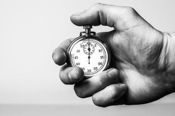 Hand holding stopwatch in black & white
