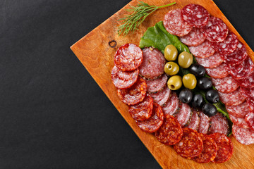 assortment smoked sausage slices on cutting board
