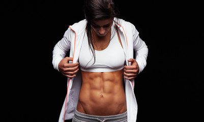 Fitness woman looking at her muscular abs