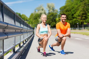 smiling couple stretching leg outdoors