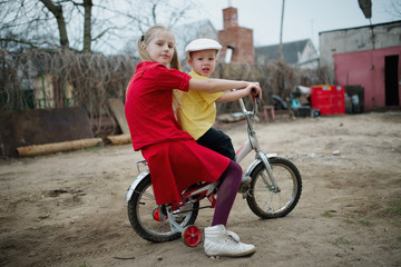 children ride on bicycle in yard