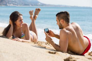 Happy couple taking photo on the beach