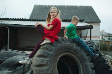 children playing in junkyard tires