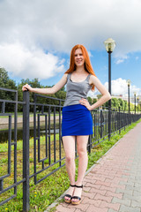 red-haired girl stands on the embankment