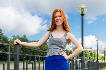 girl with red hair standing on the waterfront