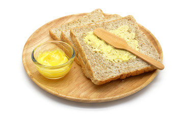 Isolated whole wheat bread and butter in a wooden bowl
