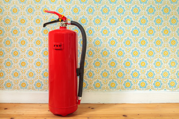 Fire extinguisher in front of retro flower wallpaper