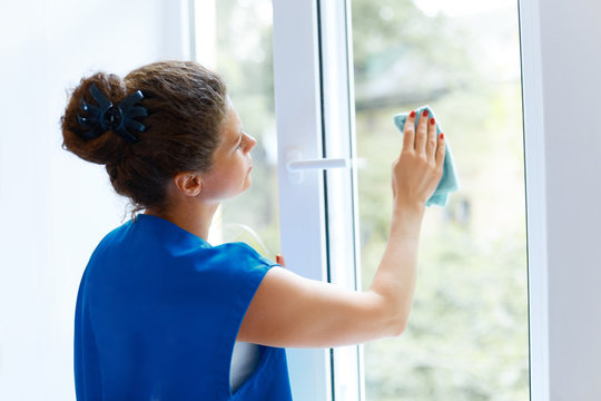 Young Woman cleaning window glass. Cleaning Company Worker