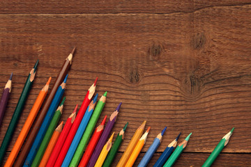 Set of Multicolor Colored Pencils or Crayons on wooden background