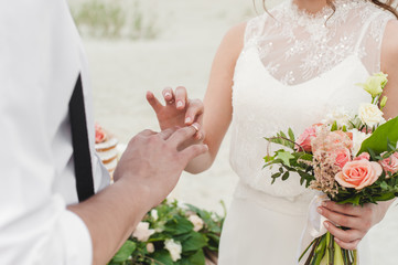 Bride wears the ring on the finger of the groom