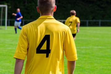 Fußballspieler im gelben Trikot von hinten