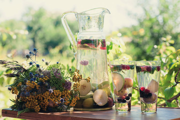 Summer cocktails with seasonal fruit in transparent glass carafe stands on a table in a garden next to a glass beaker with a drink of vegetarian food