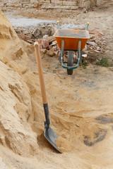 Shovel and wheelbarrow with sand