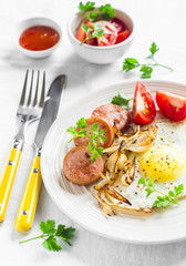 fried egg, sausage, tomatoes - tasty Breakfast or snack, on the bright plate on a light wooden background