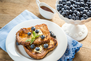 French toasts with fresh blueberries and maple syrup