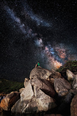 The milky way over a lonely man on rocks admiring it.