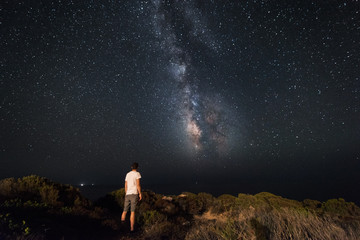 Lone man looks with amazement at the night sky with the Milky Way - horizzontal version