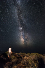 Lone man looks with amazement at the night sky with the Milky Way - vertical version