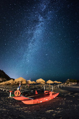 Red catamaran rescue on the beach by night under the milky way