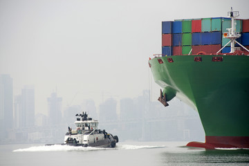 Tugboat approaching Shipping Container fully loaded with cargo coming into port