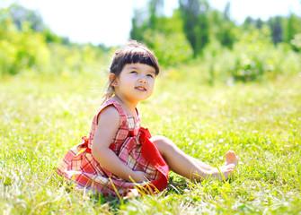 Little girl child sitting on the grass outdoors enjoying warm su