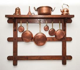 Vintage copper cookware hung on wooden shelf