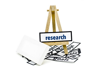 concept research word on wooden stand.random cutted print paper and empty canvas frame isolated white background