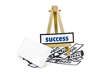 concept success word on wooden stand.random cutted print paper and empty canvas frame isolated white background