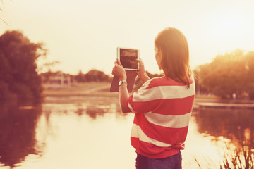 girl holding digital tablet pc taking photo at lake shore in sun