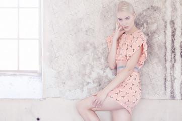 Slim fashion blond model in pink dress.