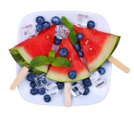 Watermelon popsicle and blueberries on plate isolated on white