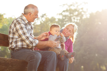 Grandparents with grandson enjoying the sunny autumn day in park.