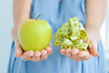 Young woman holding an Apple and a measuring tape suggesting diet concept