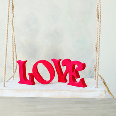 Decoration elements, wooden red love letters on the swing