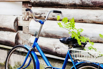 Old blue bike standing near the wooden wall