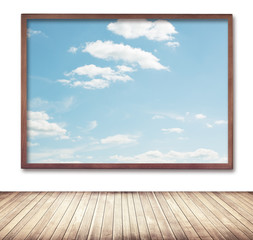 Wooden frame with cloud and sky picture hanging on wall near