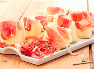 sweet melon with serrano ham cut on chips and sliced
