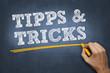 """Hand schreibt mit Kreide Text """"TIPPS&TRICKS"""" auf Tafel"""
