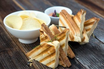 Toast sandwiches with ham on the wooden board.