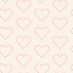 Pink dotted hearts on cream-colored background seamless pattern